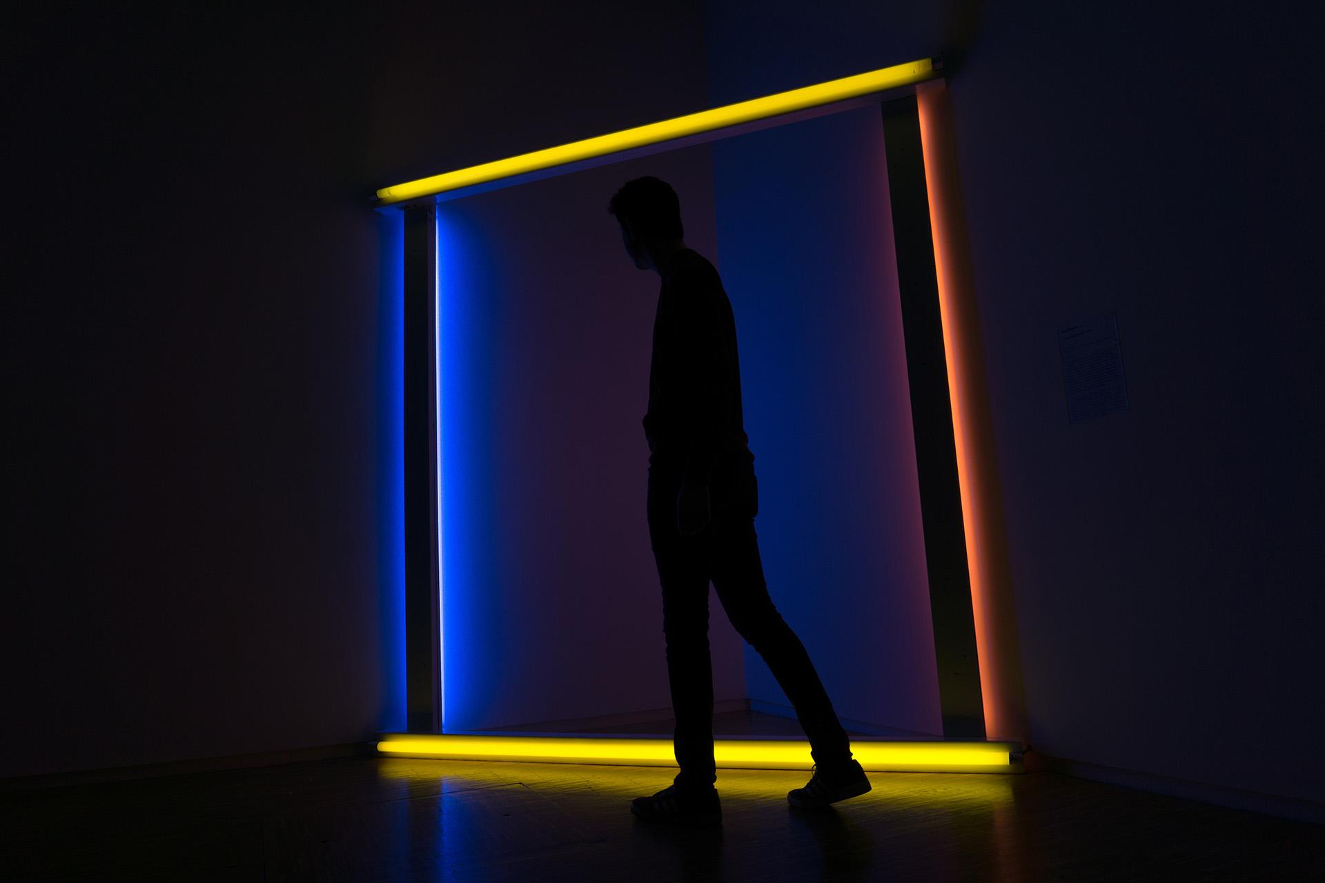 man walking in front of neon door