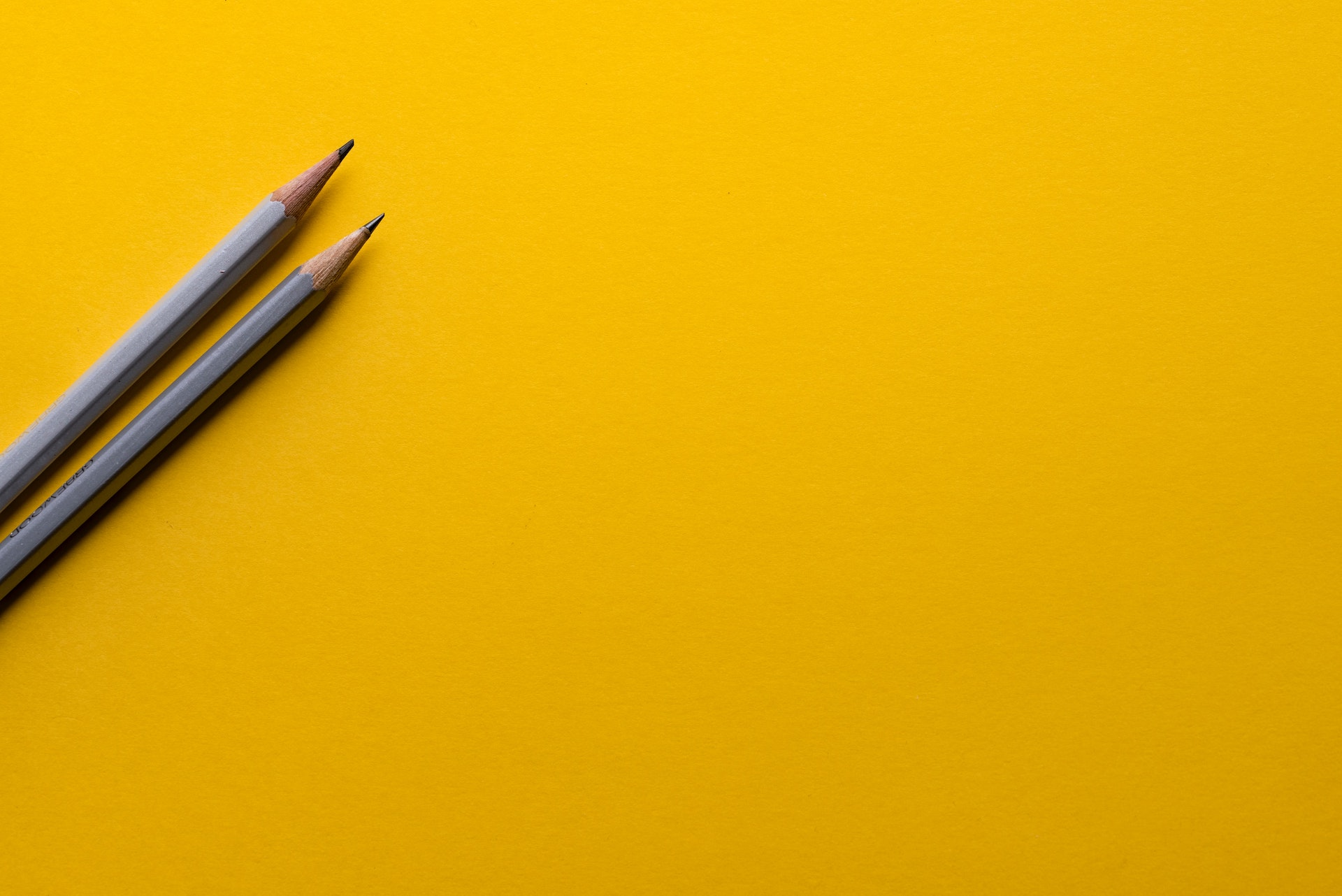 two pencils on plain yellow background