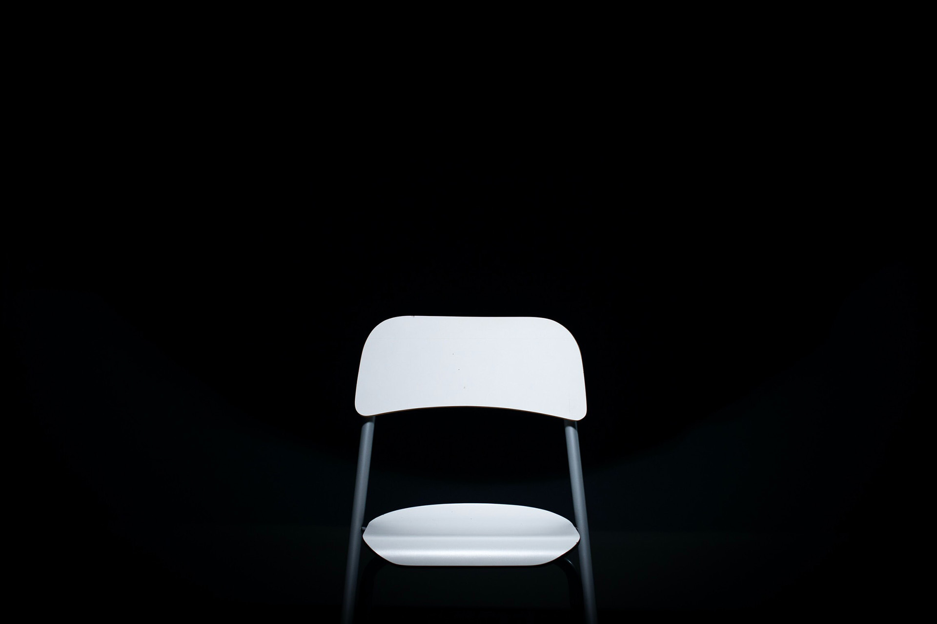 White chair in a black room