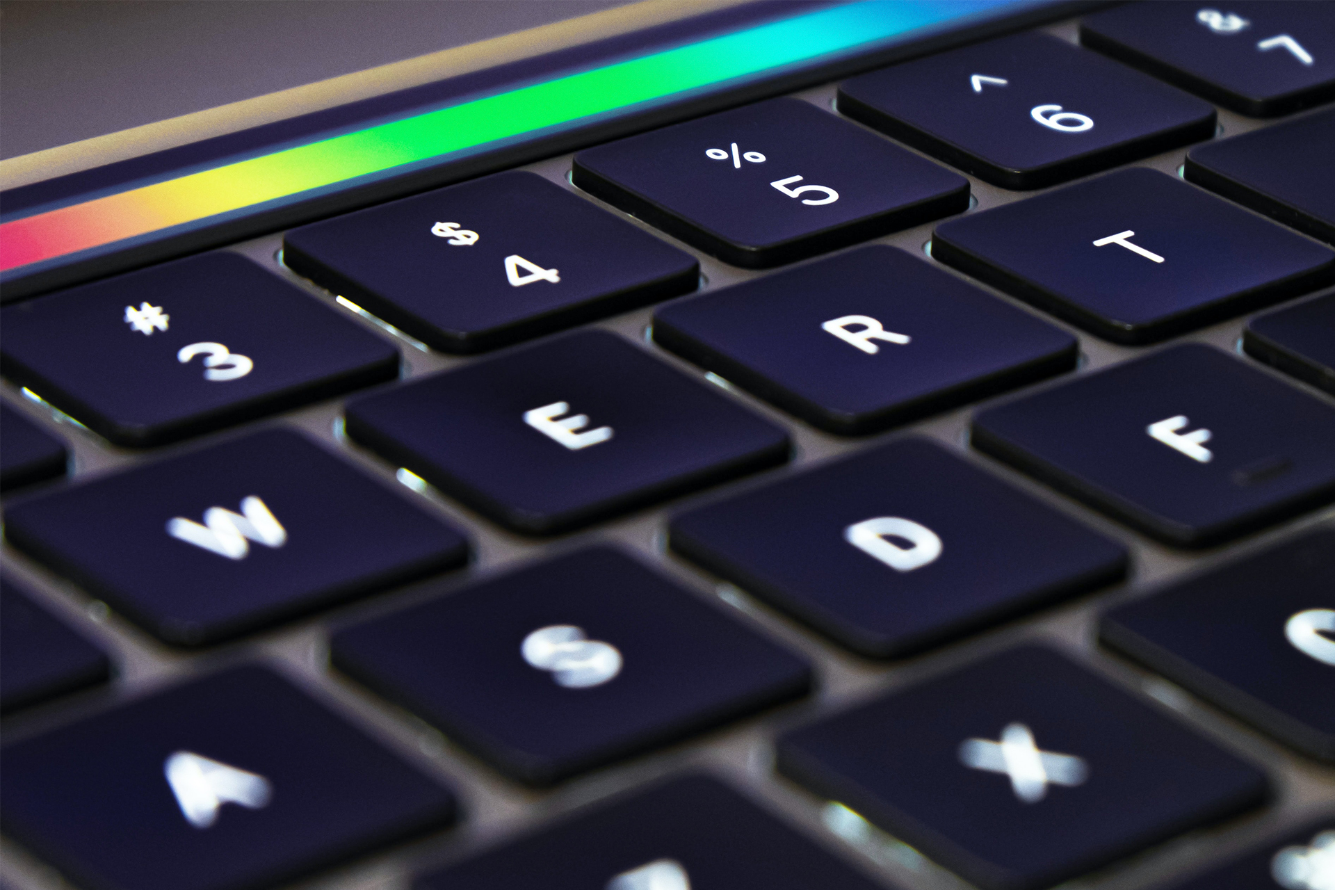 laptop keyboard with strip of rainbow color